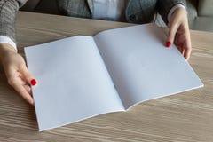 Het meisje houdt ter beschikking het tijdschriftmodel het A4-formaat stock foto