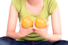Het meisje houdt twee sinaasappelen bij een borst. Royalty-vrije Stock Foto
