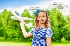 Het meisje houdt vliegtuigstuk speelgoed op het groene gebied Stock Foto's