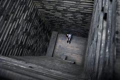 Het meisje in houten goed Eenzaamheid en wanhoop Vreemde archetekturnoebouw stock afbeeldingen