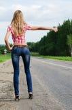 Het meisje in jeans houdt de auto op weg tegen Stock Afbeelding