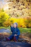 Het meisje in jeanskleren werpt gelukkig de herfstbladeren Stock Foto's
