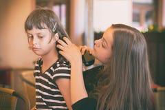 Het meisje kamt haar haar aan haar vriend Stock Afbeeldingen