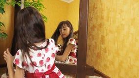 Het meisje kamt haar haar door de spiegel Het meisje kamt haar haar Het kind zit door de spiegel stock videobeelden