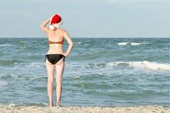 Het meisje in Kerstmanhoed en badpak onderzoekt de afstand Overzees royalty-vrije stock foto's