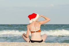 Het meisje in Kerstmanhoed met het inschrijvingsnieuwjaar op de rug zit op het strand en onderzoekt de afstand stock afbeeldingen