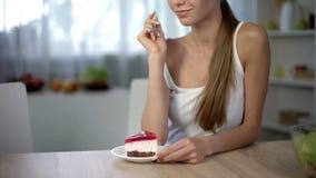 Het meisje kiest cake in plaats van salade, verleiding ophouden op dieet zijnd, ongezond voedsel stock foto