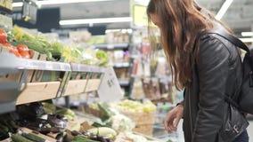 Het meisje kiest groenten in de supermarkt