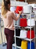 Het meisje kiest spoelen met draden in opslag Stock Foto