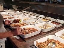 Het meisje kiest het voedsel in een Aziatische restaurant loon-wat-u-Behoefte onder de talrijke egozotic schotels kiest Keuken tu stock foto's