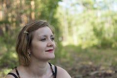 Het meisje kijkt aan de hemel Vrouw die zijdelings in een park in de zomer kijken Royalty-vrije Stock Foto's