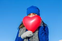 Het meisje kijkt behandelend gezichtsballon in de vorm van hart Royalty-vrije Stock Foto's
