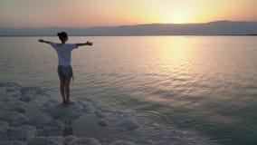 Het meisje kijkt in de richting van de zonsopgang stock videobeelden