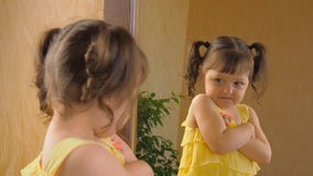 Het meisje kijkt in de spiegel Een mooi meisje met staarten op haar hoofd vlamt een oog op Een kind in a stock footage