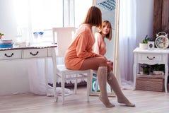 Het meisje kijkt in de spiegel Vrouw en spiegel in het binnenland De bezinning in de spiegel royalty-vrije stock afbeelding