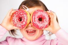 Het meisje kijkt door donuts Stock Foto's
