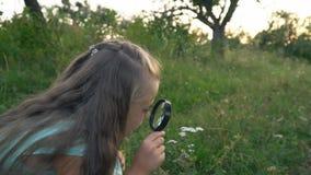 Het meisje kijkt door een vergrootglas stock footage