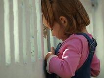 Het meisje kijkt door een witte omheining royalty-vrije stock afbeeldingen