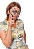 Het meisje kijkt door meer magnifier Stock Afbeeldingen