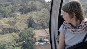 Het meisje kijkt door het venster in de kabelbaan - Tbilisi, Georgië stock footage