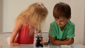 Het meisje kijkt een microscoop stock footage