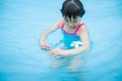 Het meisje kijkt een witte bloem in de pool royalty-vrije stock afbeelding