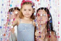 Het meisje kijkt erachter, haar ouderstribune Stock Fotografie