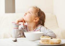 Het meisje kijkt met afschuw voor voedsel Stock Foto's
