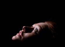 Het meisje kijkt omhoog in dark Stock Afbeeldingen