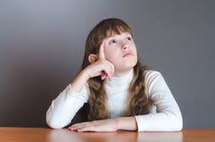 Het meisje kijkt omhooggaand en denkt Stock Afbeelding