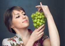 Het meisje kijkt op druiven Stock Afbeeldingen