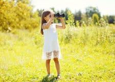 Het meisje kijkt in openlucht in verrekijkers in de zomer Stock Afbeeldingen