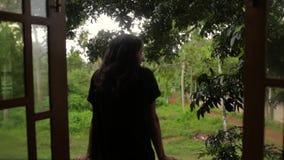 Het meisje kijkt uit haar bungalow stock videobeelden