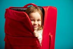 Het meisje kijkt uit rode koffer op blauw ge?soleerde achtergrond stock afbeelding