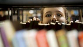 Het meisje kijkt uit van achter de boeken stock video