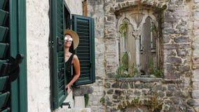 Het meisje kijkt uit het venster met groene blinden van een oud huis stock footage