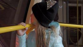 Het meisje kijkt uit het venster van de auto in de metro stock video
