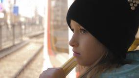 Het meisje kijkt uit het venster van de auto in de metro stock footage