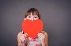 Het meisje kijkt van onder hart Stock Foto's