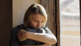 Het meisje kijkt zeer droevig terwijl het luisteren muziek op hoofdtelefoons door het venster stock foto