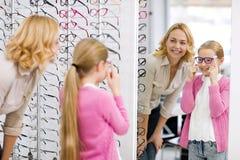 Het meisje kijkt zelf in de spiegel met nieuwe eyewear royalty-vrije stock foto