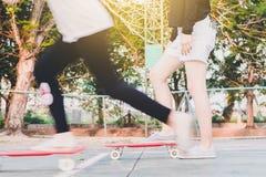 het meisje is klaar aan het ertoe brengen van begin om na zustermovin met een skateboard te rijden stock afbeeldingen