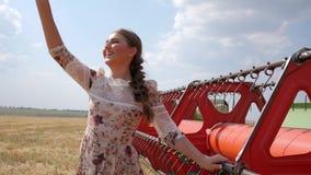Het meisje in kledings golvende hand Hello in langzame motie naast landbouw combineert stock videobeelden