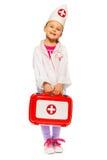 Het meisje kleedde zich als een arts met stuk speelgoed eerste hulpuitrusting Stock Afbeelding