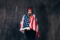 Het meisje kleedde zich in de vlag van de V.S. op donkere achtergrond Royalty-vrije Stock Foto's