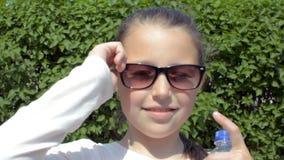 Het meisje kleedt haar glazen, golven haar hand aan de linkerzijde stock videobeelden