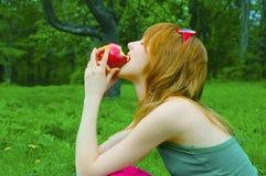 Het meisje knaagt aan appel stock afbeeldingen