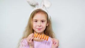 Het meisje knaagt cheerfully wortel aan stukken op een stok Kind die met konijntjesoren wortel eten stock video