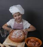 Het meisje kneedt deeg Stock Foto