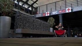 Het meisje kneedt in het midden van een winkelcentrum, langzame motie stock videobeelden